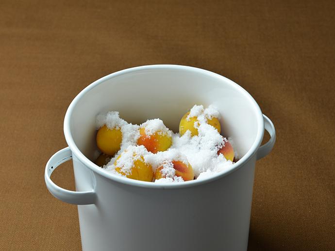 「<p>まんべんなく塩をまいた容器に、梅と塩2/3を交互に入れ、一番上に焼酎をまいてから残りの塩を均一に入れます。</p> 」の補足画像